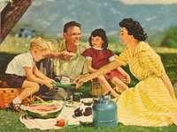 Gemälde. - Ein Familienpicknick in den Bergen. Eine Gruppe von Menschen, die mit Essen an einem Tisch sitzen.