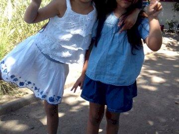 plac i siostry - 2 lalki 2 osoby. Mała dziewczynka pozuje do zdjęcia.