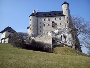 Bobolice Castle - Bobolice Castle. Trail of the Eagles' Nests. A stone castle with a clock at the top of a gra
