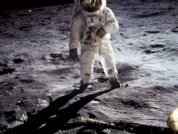 Astronaut - Astronaut walking on the moon. A person riding a bike down a dirt road.