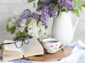 Wieczór z książką - uroczy wieczór z książką  przy kawie. Bukiet kwiatów w wazonie na stole.