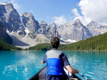 Moraine Lake - Mann, der nahe Berg und Wald Kajak fährt. Eine Person, die vor einem See steht.