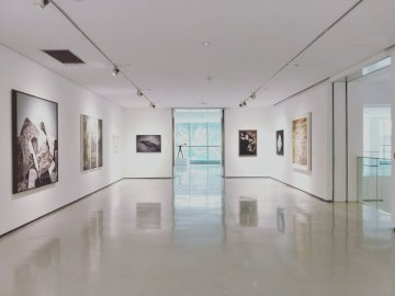An art gallery that is close by - Assorted paintings on white painted wall. China. A large empty room.