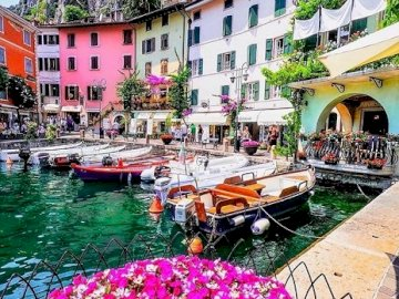 Italy. Limone. - Italy. The charming landscape of Limone. A row of colorful umbrellas sitting next to a building.