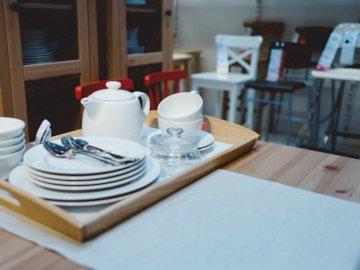 Esposizione salone Ikea - set di - Tazza in ceramica bianca su piatto in ceramica bianca. Mosca. Un computer portatile che si siede sop