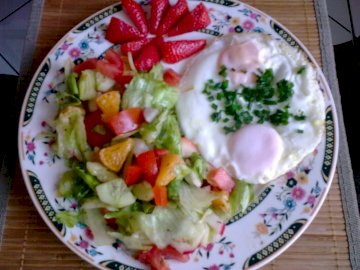 Insalata con uovo - insalata, uovo, frutta, piatto. Un piatto di cibo su un tavolo.