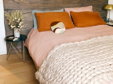 Pink bedroom - Pink and orange in the bedroom, blanket. A large bed sitting in a room.