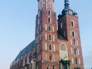 panorama - St. Mary's Church in Krakow. A large brick building with a clock tower.
