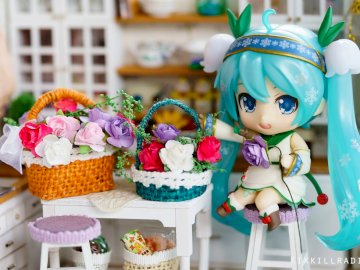 Miku and pretty flowers - Miku in his well-flowered house. A colorful toy on a table.