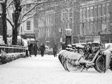 Neige à Londres - Ville couverte de neige. Une personne chevauchant une calèche dans une rue de la ville.