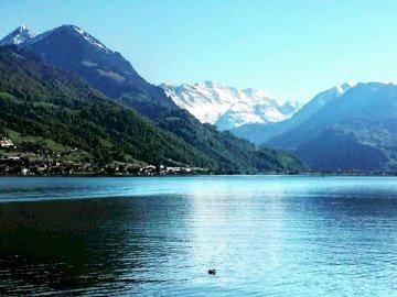 Switzerland Zug - Body of water near mountain during daytime. Switzerland. A body of water with a mountain in the back