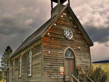 drewniany kościół - Stary drewniany kościół w dolinie. Kościół z zegarem na szczycie trawiastego pola.