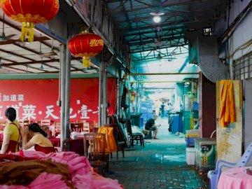 Un collègue qui est un - Deux lanternes chinoises rouges suspendues au plafond. Un groupe de personnes dans une pièce.
