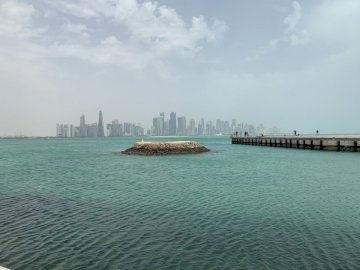 Corniche - Quai de plage grise avec vue sur la ville avec des immeubles de grande hauteur sous un ciel blanc et