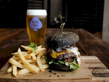 Ora di pranzo! - Hamburger e patatine fritte cotte. Un panino seduto su un tavolo di legno.