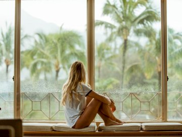 Rainy day on Kauai - Woman sitting on white cushion near glass window. Los Angeles, CA. A woman standing in front of a wi