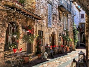A street in a small town. - A small street in an Italian town. A stone building that has a clock on the sidewalk.