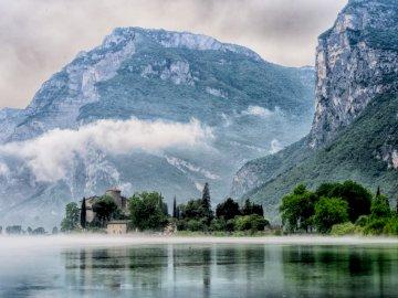 Mer de brouillard - Lac à travers montagne et arbres. Gand, Belgique. Une grande cascade sur un plan d'eau avec