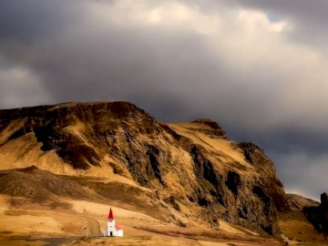 Iceland panorama - small church in the valley --------------------. A person riding on top of a mountain.