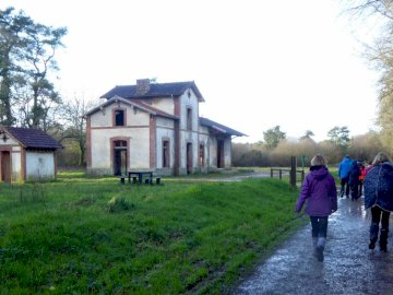 Michelbo - end of hiking station. A group of people walking on a path in front of a house.