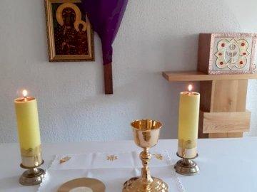 Altar - Einführungsriten - Rätsel zum Thema: Einführungsriten der Heiligen Messe. Eine Blumenvase auf einem Tisch.