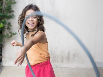 Bambole, for children - Girl playing hula hoop on his arm. Aracaju - Brazil. A young girl standing in front of a building.