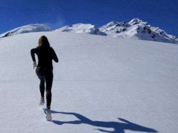 Courir vers le haut - Femme qui court sur la montagne couverte de neige. Vallée d'Aoste, Italie. Un groupe de per
