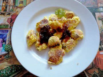 kaiserschmarrn - Omlet cesarski. Austriacki deser. Biały talerz z mięsem i warzywami.