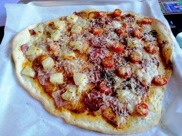 Pizza Hani - Domowa pizza, na cienkim spodzie. Na stole siedzi pizza.