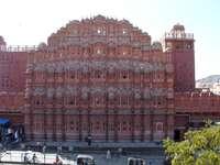 vindens palats i jaipur - vindens palats i jaipur. En stor tegelbyggnad med många fönster med Hawa Mahal i bakgrunden.