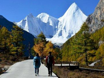 Toeristen in de bergen - Toeristen in het hooggebergte. Een groep mensen lopen langs een besneeuwde berg.