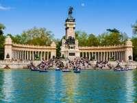 PARQUE DEL RETIRO - El parque del Retiro v Madridu. Malá loď v těle vody obklopená stromy s Buen Retiro Park v pozad