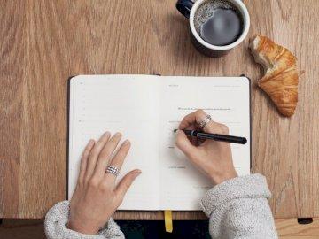Skrivande i en tidskrift - Person som skriver på en bok. Austin, Texas. En person som sitter på ett träbord.