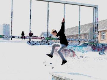 W akcji - Człowiek na deskorolce na ziemi. Bruksela. Mężczyzna skacze w powietrzu robiąc lewę na deskorol