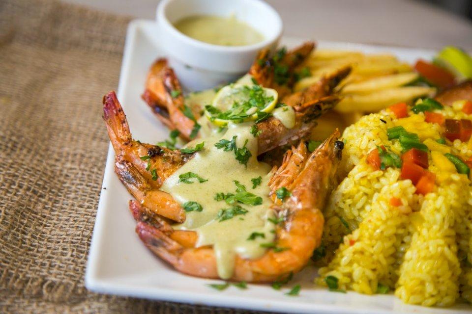 Grillowany kurczak - Krewetki z sosem śmietanowym i ryżem warzywnym. Talerz jedzenia na stole.