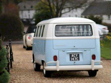 Wesela - Biały Volkswagen T-2 na drodze w ciągu dnia. Biały samochód przed ciężarówką.