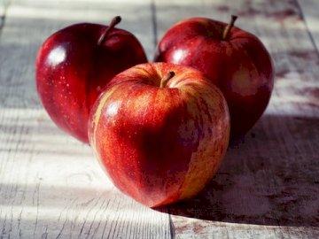 Tres manzanas - Los rompecabezas representan tres manzanas. Una manzana roja sentado encima de una mesa de madera.