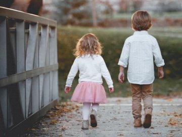 Camminando nel parco - Ragazzo accanto alla ragazza che cammina vicino all'inferriata. Una bambina in piedi accanto