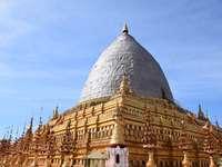 stupa efter jordbävningen i Bagan - stupa efter jordbävningen i Bagan. Ett stort klocktorn framför en byggnad.