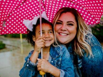 Córka mamusi - Kobieta w niebieski denim kurtka gospodarstwa parasol uśmiecha się. San Diego. Troszkę dziewczyna