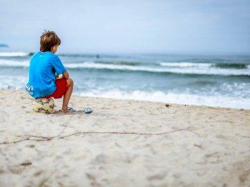 Kind sitzt auf dem Fußball - Junge, der auf Ball sitzt, während er auf den Ozean starrt. Sao Paulo. Ein kleiner Junge, der auf e