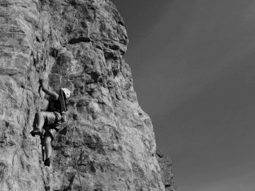 On the wall - Grayscale photography of man climbing rock. Muskoka. A man standing on a rocky hill.
