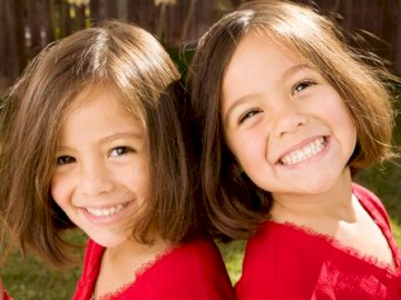 Twins - Twin sisters. A close up of a girl smiling and posing for the camera.