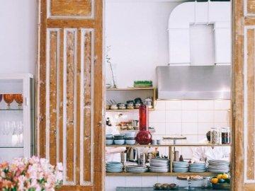 Helle Küche - Idee für eine helle Küche. Eine Küche mit Holzmöbeln und Blumenvase auf einem Tisch.