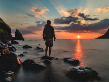Taking photos of sunsets is - Man standing on stone looking at sunset. United Kingdom. A man standing next to a body of water.