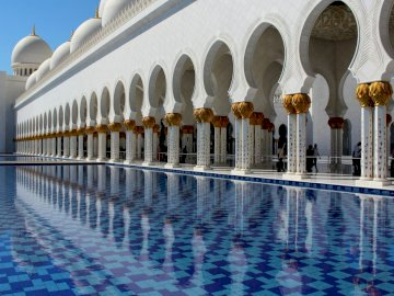 Mosque - white columns - white and blue -------------------. A large white building.