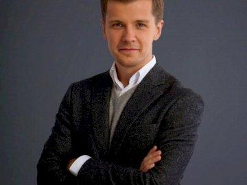 Radosław Kotarski - żródło: youtube Radosław Kotarski. Młody mężczyzna w garniturze i krawacie.