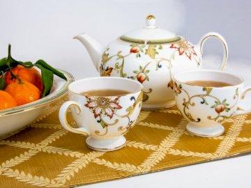 Herbata dla dwojga z delikatną porcelaną - Biało-wielokolorowe kubki wypełnione herbatą obok owoców. Dolina Krzemowa. Filiżanka kawy na st