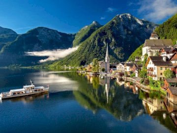 Hallstatt panorama - mountain landscape of Austria. A small boat in a body of water with Hallstatt in the background.