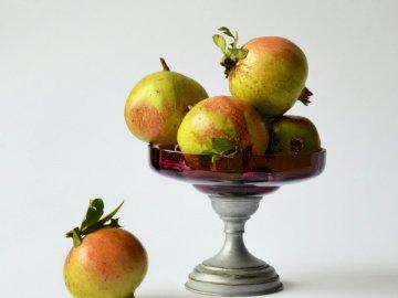Granadas y una cosecha - Tazón de durazno sobre fondo blanco. Una manzana roja sentada en una mesa.